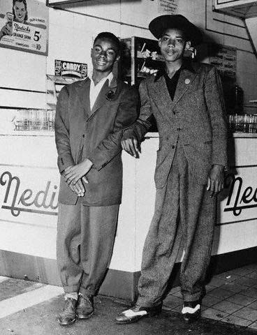 שני נערים שחורים לבושים זוט סוט נשענים על קיוסק